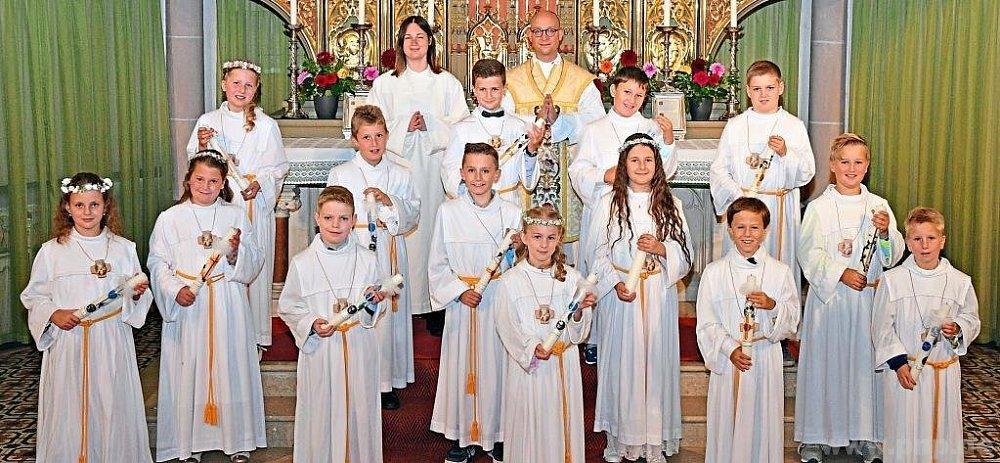 Die Kinder aus dem Gemeindegebiet Geiersthal vor dem Hochaltar der Pfarrkirche Teisnach mit Pfarrer Tobias Magerl (hinten Mitte) und Gemeindereferentin Steffi Haimerl (links daneben)